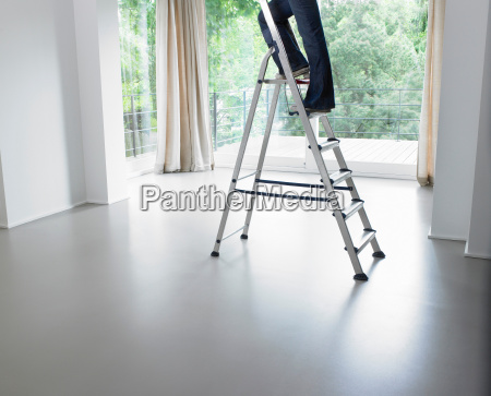 woman on a ladder in living