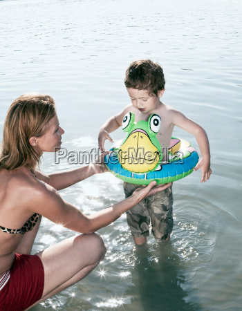 mother fitting childs swimming ring