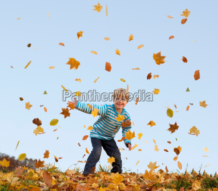 boy throwing autumn leaves into the