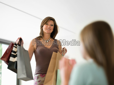 mother showing shopping to teenage girl
