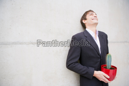 man in suit holding a cactus