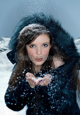 woman blows snow from hand