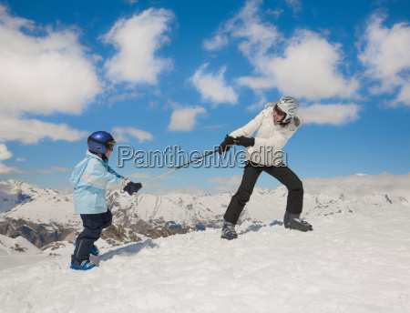 woman pulling boy up snowy hill
