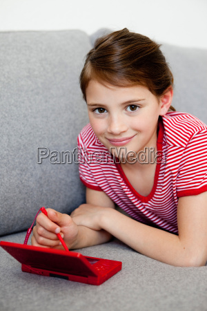 girl playing video game on couch