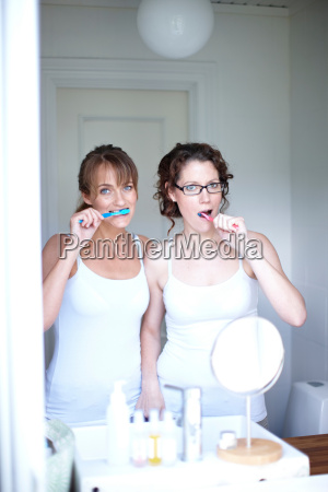 two women brushing teeth