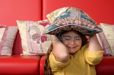 young girl hiding under cushion