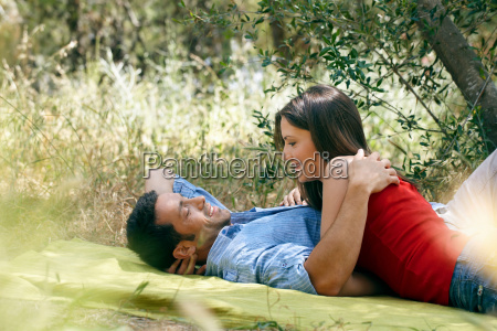couple cuddling on picnic blanket