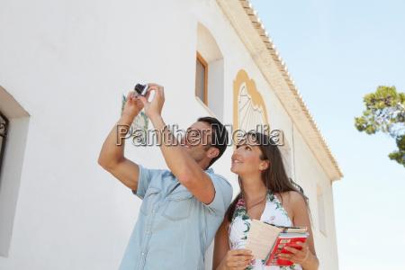 tourist couple taking snapshot of church