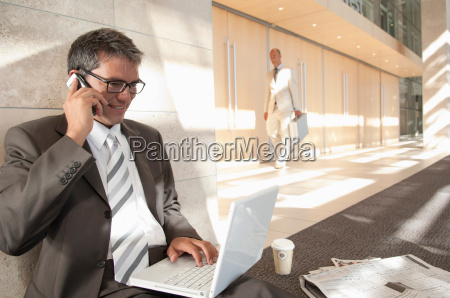 business man on laptop and phone
