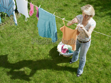 woman hanging clothes on clothesline