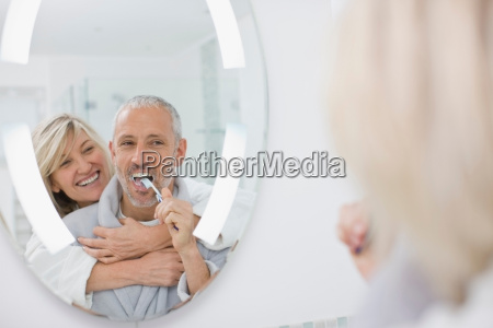 man brushing his teeth with wife