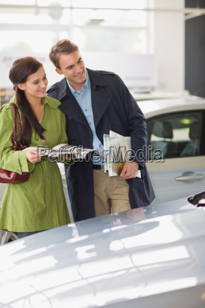 couple admiring car in showroom