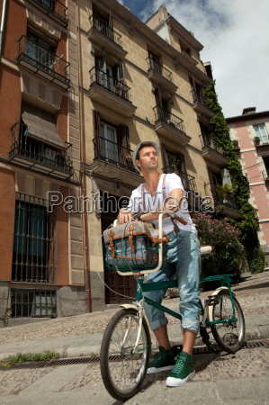 man sitting on bike on city