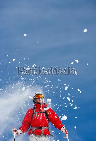 snow spraying over male skier