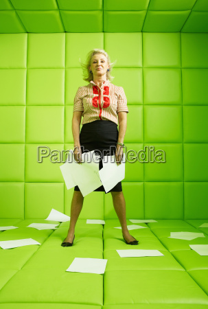woman standing with papers around her