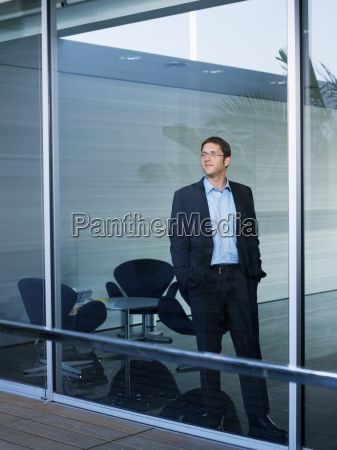 young businessman at window in office
