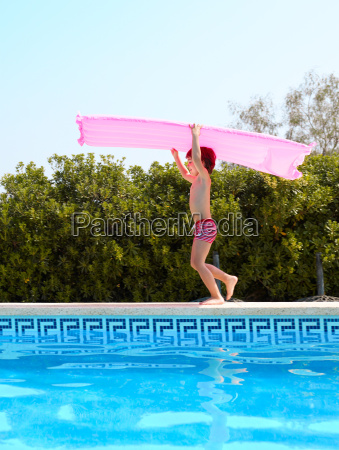 boy running by swimming pool