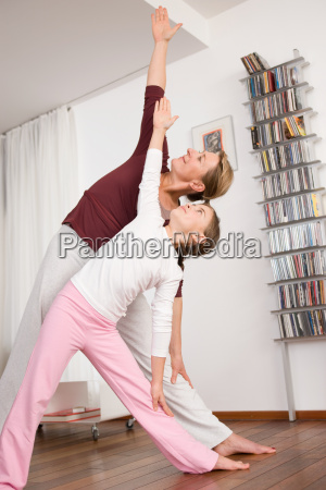 mother and girl doing yoga together