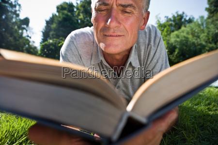 man lying on grass reading