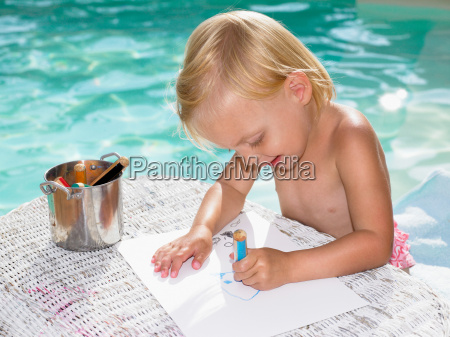young boy coloring by a pool