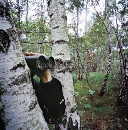 man peeking from behind a tree