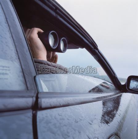 man with binoculars peeking through car
