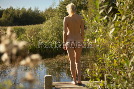 young woman nude on jetty by