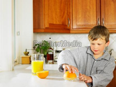 young boy making orange juice in