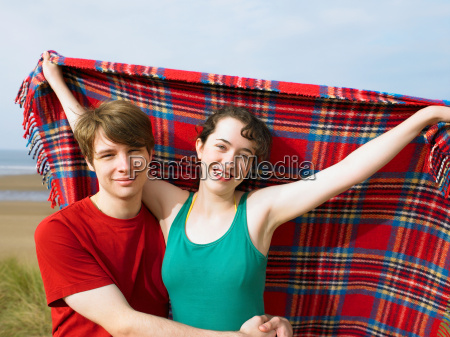 man hugging woman holding blanket