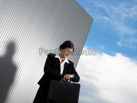 businesswoman by a silver wall