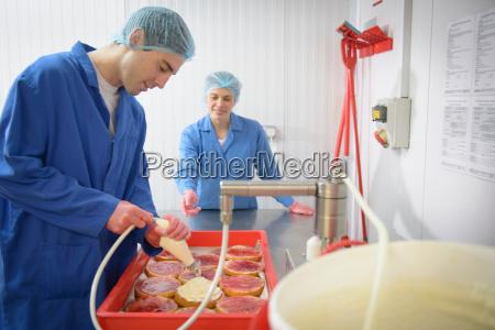 baker guiding trainee in adding cream