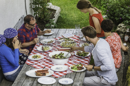 friends sitting down to picnic lunch
