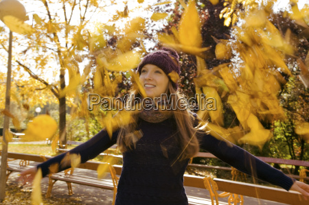 young woman throwing up autumn leaves