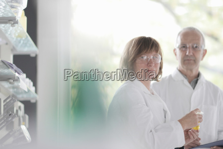 scientists working in laboratory holding vial