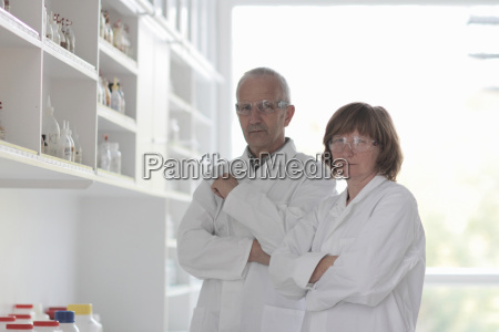 scientists working in laboratory arms folded