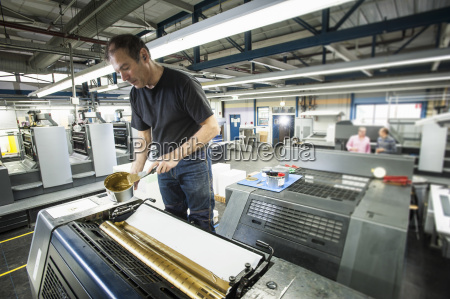 worker applying gold ink to printing