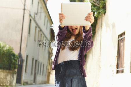girl photographing with digital tablet on