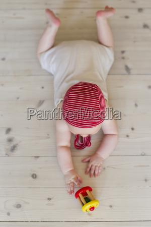 baby girl lying on floor with