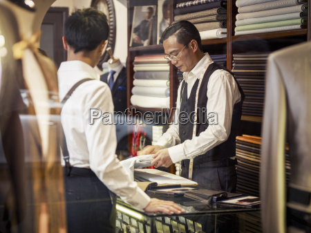 father and son looking at fabric