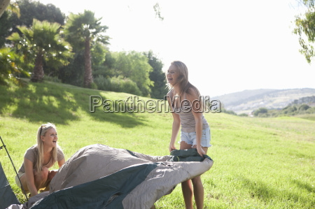 two young females friends unwrapping tent