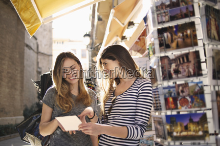 young female friends looking at postcards
