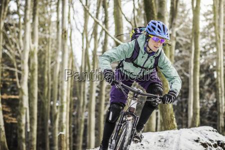 female mountain biker riding through forest