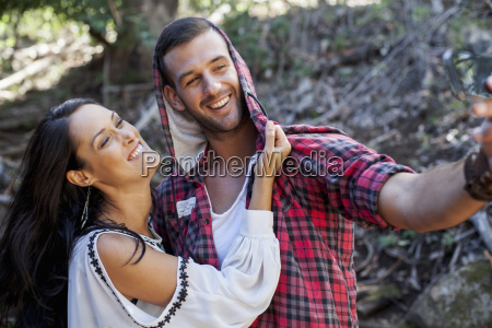 young couple fooling around in forest