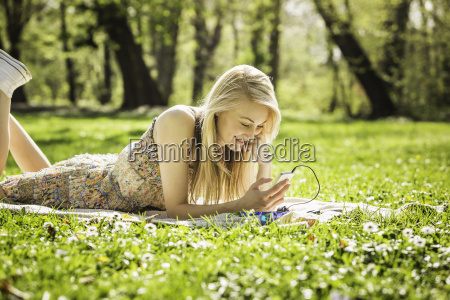 young woman lying in forest looking