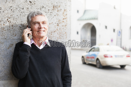 senior man chatting on smartphone on