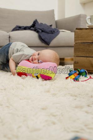 baby girl lying on rug with