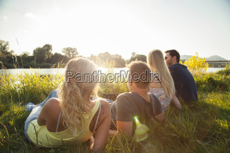 four young adult friends reclining on
