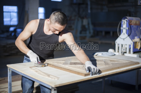 carpenter piecing together wood blocks in