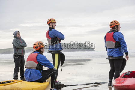 four people on beach with kayaks