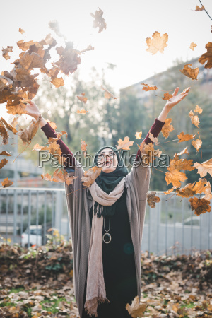 young woman throwing autumn leaves in